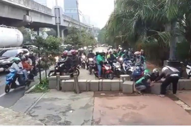 Sejumlah pengendara sepeda motor bergotong royong menggeser beton pembatas di trotoar Jalan Casablanca, Jakarta Selatan, tepatnya di depan Taman Pemakaman Umum Menteng Pulo. Aksi mereka terekam kamera dan videonya kini beredar di media sosial.