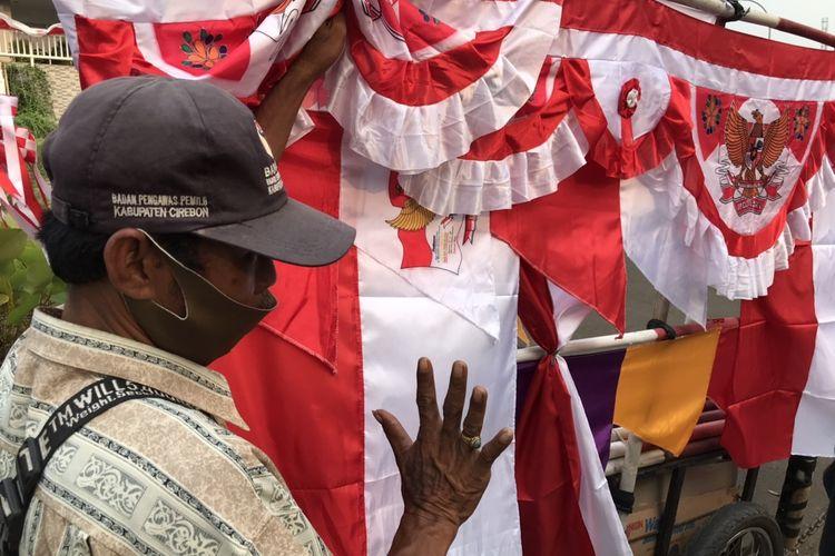 Surjana (72), penjual bendera Merah Putih di pinggir Jalan Raya Lenteng Agung, Jagakarsa, Jakarta sedang berbincang dengan calon pembeli. Surjana mulai berjualan bendera Merah Putih sejak ia berumur 10 tahun.