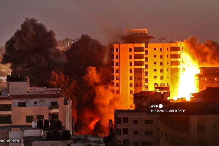 Asap mengepul dari gedung Hanadi di <a href='https://manado.tribunnews.com/tag/gaza' title='Gaza'>Gaza</a> City, setelah serangan udara yang dilakukan <a href='https://manado.tribunnews.com/tag/israel' title='Israel'>Israel</a> pada 11 Mei 2021.
