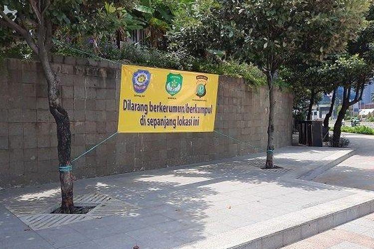 Sebuah spanduk berwarna kuning bertuliskan 'Dilarang berkerumun atau berkumpul di sepanjang lokasi ini,' terpajang di sepanjang trotoar Hotel Mandarin, Menteng, Thamrin, Jakarta Pusat, Jumat (5/3/2021).