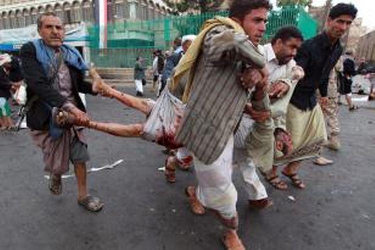 Anggota milisi Huthi menggotong seorang korban bom bunuh diri yang meledak di kerumunan pendukung pemberontak Syiah di ibu kota Yaman, Sanaa.