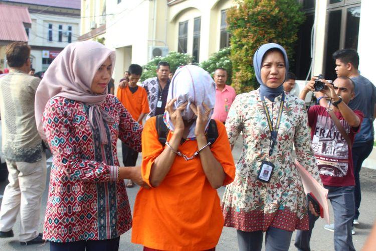 Polisi membawa tersangka UG, ibu yang menyuruh anaknya mengemis di Mapolres Lhokseumawe, Aceh, Jumat (20/9/2019)