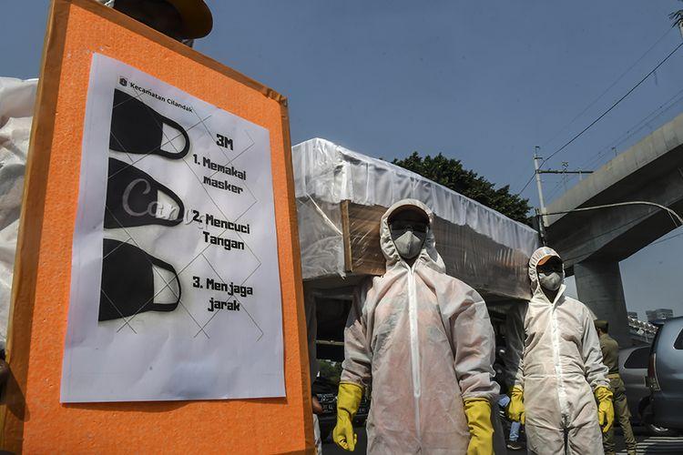 Petugas Kecamatan Cilandak membawa peti jenazah saat melakukan kampanye bahaya COVID-19 di Jakarta, Senin (31/8/2020). Dalam kampanye tersebut petugas mengimbau sekaligus mengajak masyarakat baik pengguna jalan maupun warga untuk selalu melakukan gerakan 3M yaitu Menggunakan Masker, Mencuci Tangan dan Menjaga Jarak.