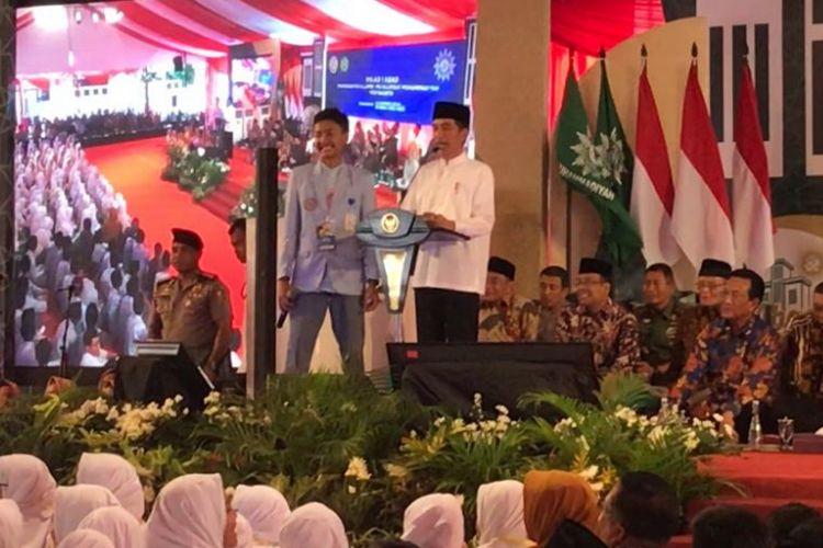 Presiden Joko Widodo saat bertanya kepada siswa Madrasah Muallimin-Muallimat Muhammadiyah Yogyakarta Indrawan Diko saat acara milad 1 abad madrasah itu, Kamis (6/12/2018).