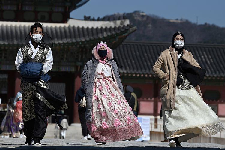 Orang-orang dengan pakaian tradisional Korea mengenakan masker wajah saat mengunjungi Istana Gyeongbokgung di Seoul, Korea Selatan, menyusul meluasnya wabah virus corona di negara itu, Minggu (23/2/2020). Penyebaran virus corona hingga hari ini, Senin (24/2/2020), semakin menunjukkan peningkatan di sejumlah negara, seperti Italia, Iran, dan Korea Selatan.