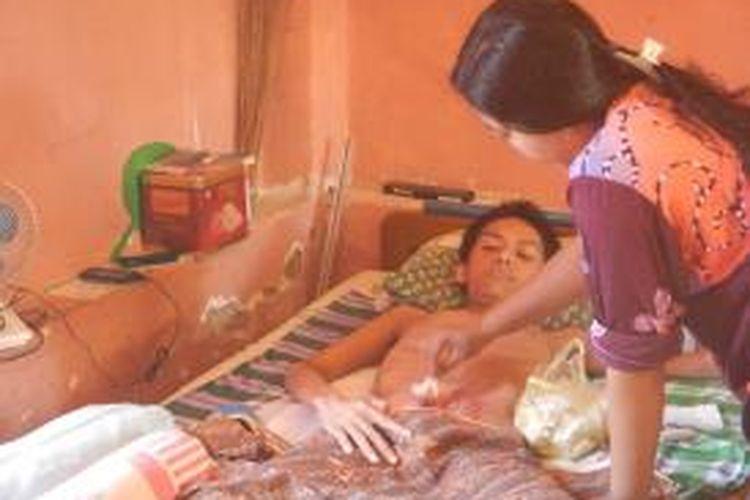 Kondisi Nasihul saat lobang di perutnya dibersihkan oleh salah satu kerabatnya. Nasihul di vonis terkena penyakit TBC usus