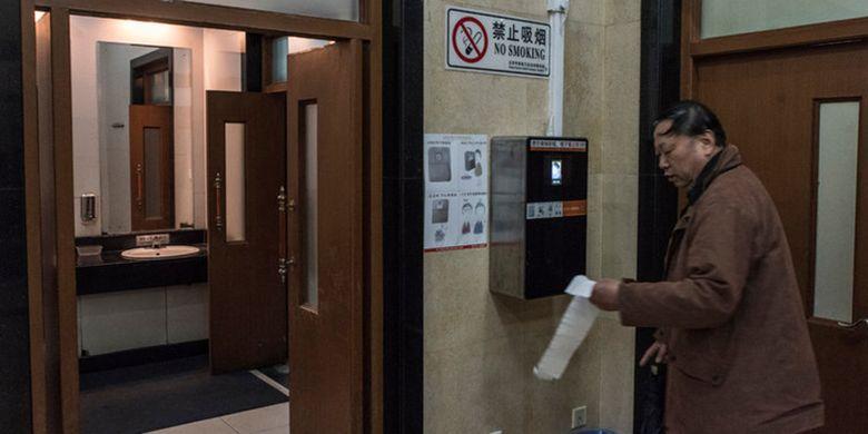 Pengunjung di toilet Temple of Heaven Park, Beijjing, China, mengambil tissue dari alat dispenser yang dilengkapi kamera pengenal wajah.