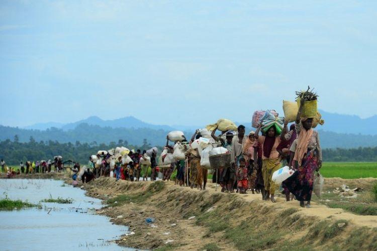 Para pengungsi Rohingya berjalan menyusuri daerah tak bertuan antara Bangladesh dan Myanmar di kawasan Palongkhali. Foto ini diambil pada 19 Oktober 2017.