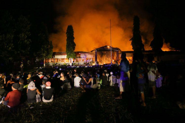 Narapidana dan tahanan dikumpulkan di halaman saat terjadi kebakaran di Rumah Tahanan Donggala, Sulawesi Tengah, Minggu (30/9/2018) pasca kerusuhan tahanan. Kerusuhan dipicu permintaan narapidana dan tahanan dibebaskan untuk menemui keluarga yang terkena musibah gempa tidak dipenuhi. Sekitar 100 tahanan dikabarkan melarikan diri.