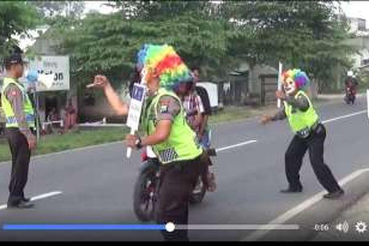 Dua polisi dengan topeng badut tampak sedang mengampanyekan tertib berlalu lintas di Tuban.