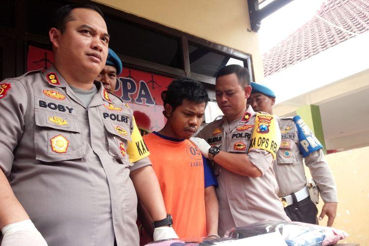 Adi Indra Purnama diapit oleh Kapolres Jombang, AKBP Bobby P Tambunan (kiri) dan Wakapolres Jombang, Kompol Budi Setiono (kanan), di depan Kantor Unit Perlindungan Perempuan dan Anak (PPA) Polres Jombang, Jawa Timur, Sabtu (2/11/2019).