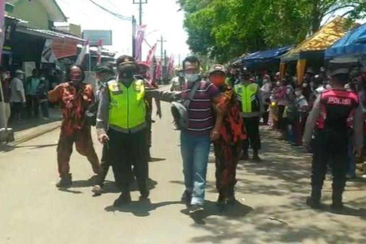 Polisi mengamankan seorang warga yang diduga akan membentangkan poster saat rombongan Presiden Jokowi melintas di Jalan Ketapang, Cilacap, Jawa Tengah, Kamis (23/9/2021).