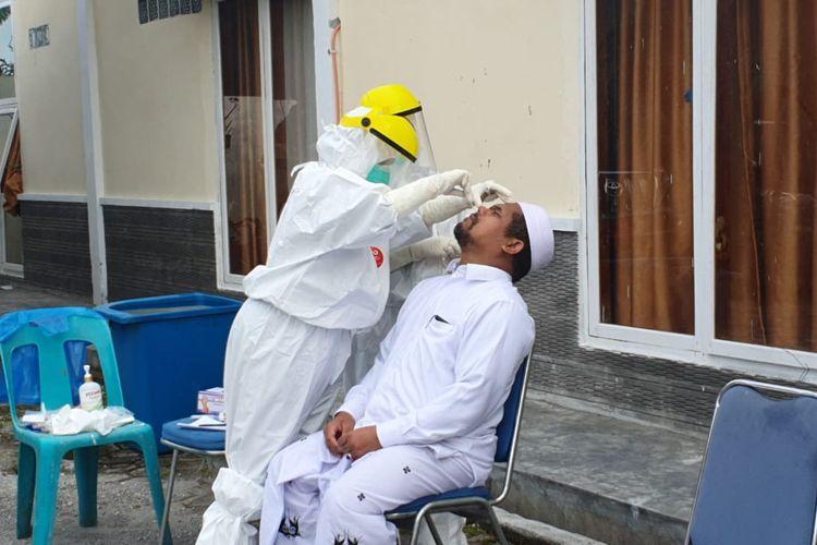 Proses pengambilan sampel lendir bagian tenggorokan untuk uji Swab terhadap Bupati Bener Meriah, Sarkawi.