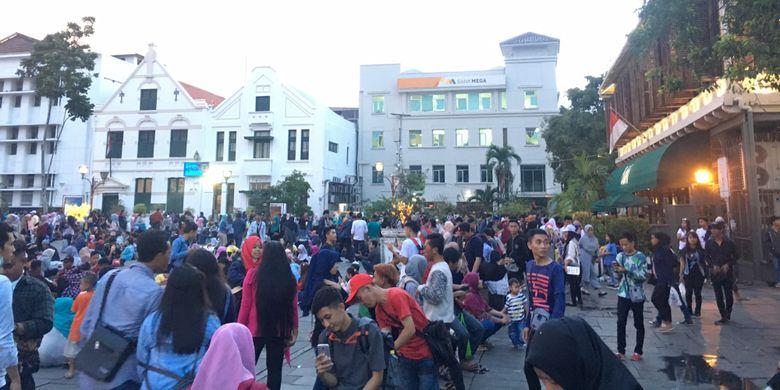 Wisata Kota Tua dipadati pengunjung, tepatnya duduk lesehan di pelataran Museum Fatahillah saat malam tahun baru 2018, Jakarta, Minggu (31/12/2017).