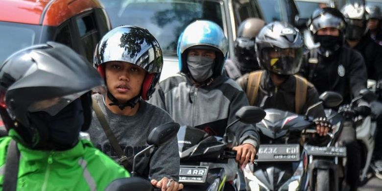 Seorang pengendara tidak menggunakan masker saat melintas di Terusan Jalan Jakarta, Bandung, Jawa Barat, Selasa (14/07).