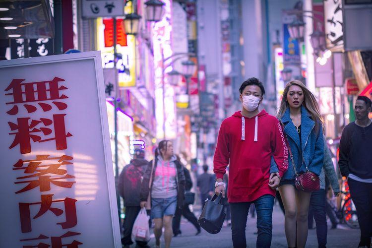 Ilustrasi seorang pria yang sedang berjalan di Harajuku mengenakan masker.