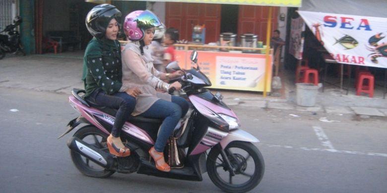 Dua perempuan yang mengenakan celana jins ketat dan duduk mengangkang mengendarai sepeda motor di Kota Lhokseumawe, Provinsi Aceh, Minggu (23/6/2013), meskipun ada larangan mengenakan celana jins ketat dan duduk mengangkang bagi kaum perempuan yang dibonceng sepeda motor.
