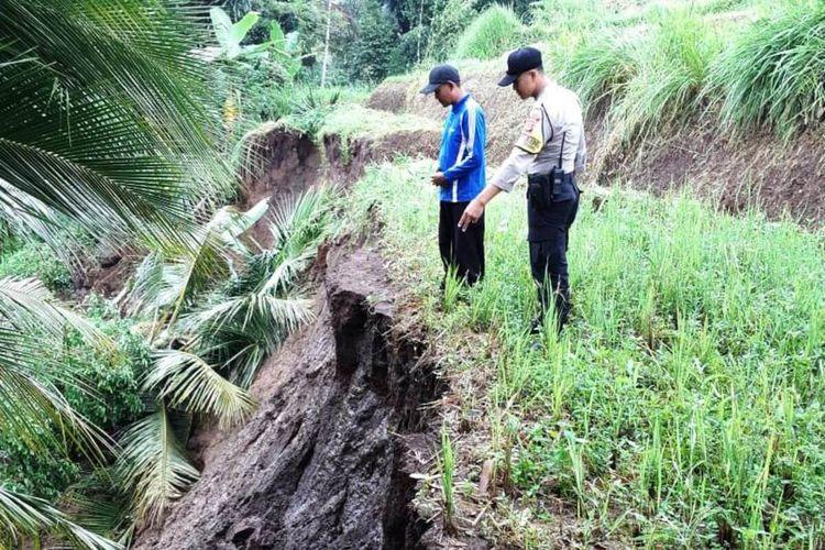 Polisi bersama warga di Cugenang, Kabupaten Cianjur, Jawa Barat meninjau lokasi tebing yang longsor di wilayah tersebut.