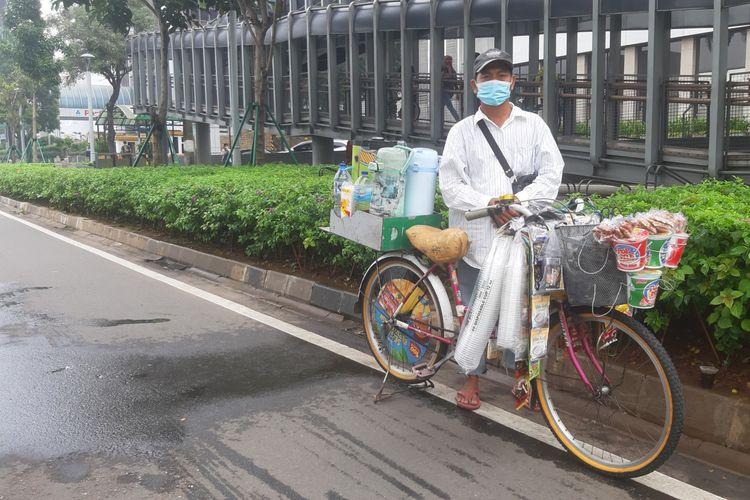 Zaini, salah seorang penjual kopi keliling saat melintas di jalur sepeda terproteksi di Jalan Sudirman, Jakarta, Sabtu (29/5/2021).