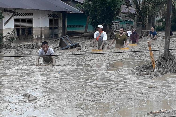 Warga melakukan pencarian klorban tertimbun lumpur akibat banjir bandang di Desa Radda, Kecamatan Baebunta, Kabupaten Luwu, Sulawesi Selatan, Selasa (14/07/2020)