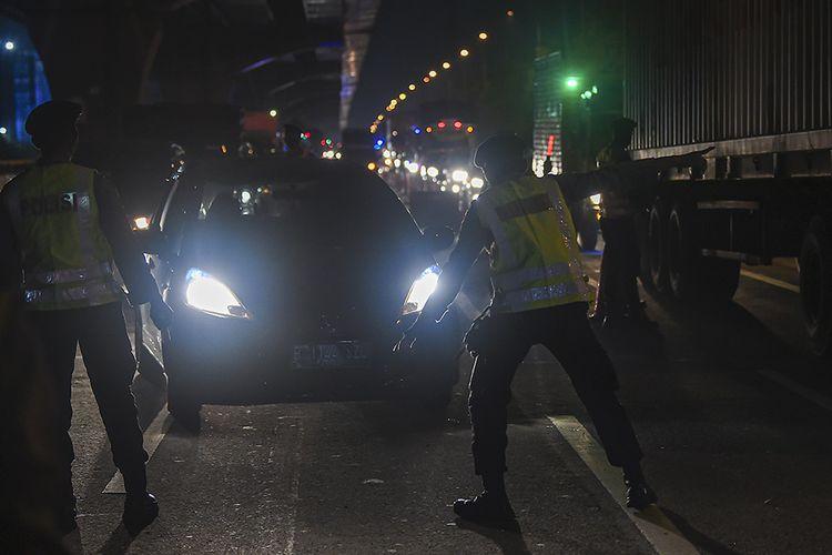 Petugas kepolisian mengarahkan kendaraan pribadi yang melintas di tol Jakarta-Cikampek untuk keluar melalui pintu tol Cikarang Barat 3, Jawa Barat, Kamis (21/5/2020). Pengalihan tersebut sebagai upaya penyekatan gelombang pemudik jelang perayaan Hari Raya Idul Fitri 1441 H dari arah Jakarta menuju Jawa Tengah.