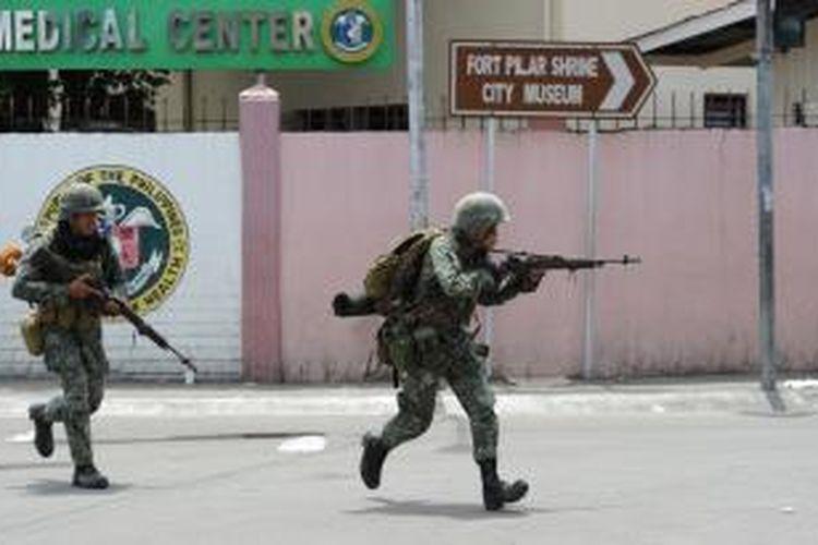 Dua prajurit Filipina berlari sambil merunduk untuk menghindari tembakan para penembak jitu pemberontak MNLF yang bersembunyi di kawasan padat penduduk di pinggiran kota Zamboanga, Filipina selatan.