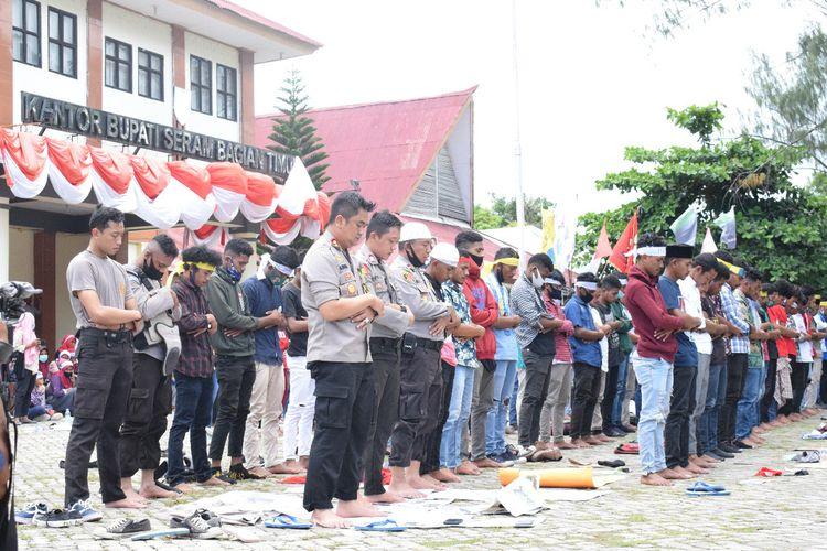 Mahasiswa dan anggota polisi melaksanakan shalat duzuhur berjamaah di depan kanto Bupati Seram Bagian Timur, Maluku Sabtu (10/10/2020). Shalat berjamaah yang diimami Penjabat Bupati Seram Bagian Barat itu dilakukan di sela-sela aksi unjuk rasa mahasiswa menolak Undang-undnag Omnibus Law Cipta Kerja di kantior tersebut