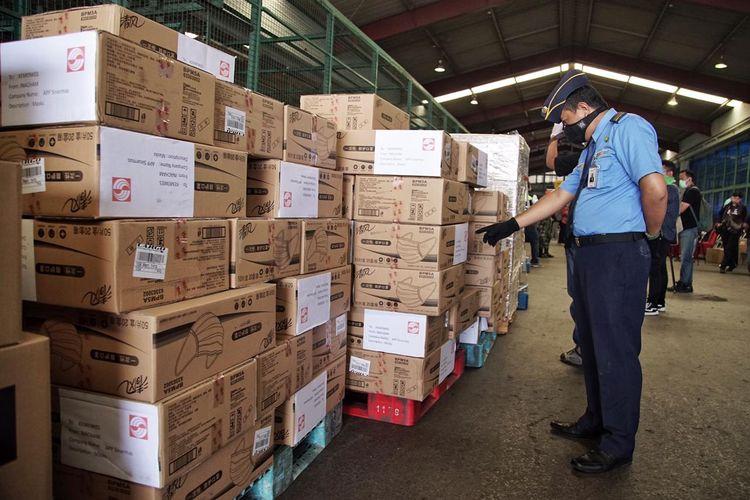 Petugas mengecek sumbangan memberikan bantuan alat kesehatan berupa masker N95, surgical masker, dan disinfectant wipes.