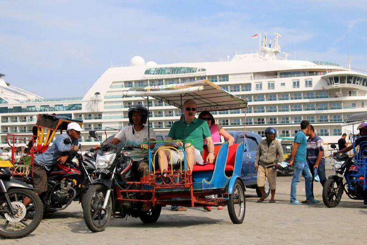 Para pelancong kapal pesiar MS Seabourn Encore mencoba menaiki becak motor, saat bersandar di Pelabuhan Teluk Sabang, Dermaga Container Terminal (CT) 3 yang berada di Gampong Kuta Timu, Sukakarya, Kota Sabang, Selasa (27/3/2018). Kapal pesiar yang mengangkut 552 wisatawan mancanegara dan 423 kru kapal itu sebelumnya menempuh perjalanan dari Phuket, Thailand dan akan kembali melanjutkan perjalanan wisata menuju Colombo, Sri Lanka.