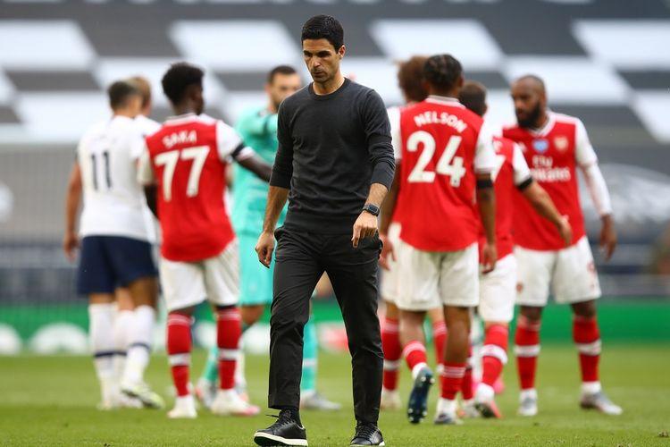 Mikel Arteta  berjalan usai kekalahan The Gunners pada laga Tottenham vs Arsenal di Tottenham Hotspur Stadium, London, Minggu (12/7/2020).