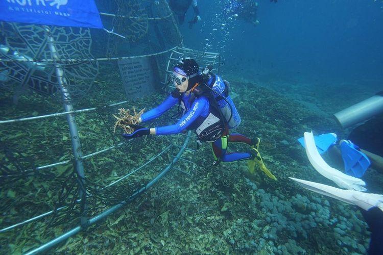 Penurunan karya instalasi dari Teguh Ostenrik di Pantai Jikomalamo, Maluku Utara.