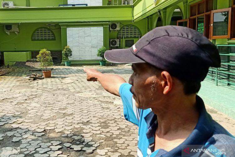 Kepala Rumah Tangga DKM Masjid Jami Uswatun Hasanah, Sartono, memperlihatkan lokasi penemuan cairan diduga air keras yang disemprotkan oknum ke lantai masjid, Senin (1/6/2020).