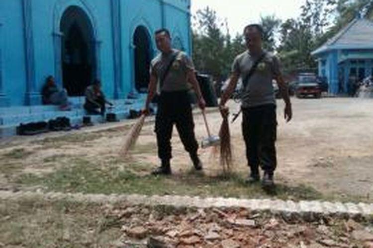 Dua di antara 500 Personil dari Polri dan TNI, Jumat (13/9/13), sedang membersihkan puing- puing kaca, serta kayu di kompleks Pondok Pesantren Darus Sholihin, Desa Puger Kulon Kecamatan Puger, Jember Jawa Timur, yang masih berserakan usai rusuh antar dua kelompok, Rabu (11/9/13) lalu.