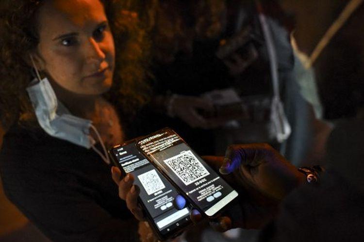 Seorang anggota staf keamanan memeriksa kartu kesehatan Covid-19, di pintu masuk kelab malam di Saint-Jean-de-Monts, Perancis barat, pada 10 Juli 2021.