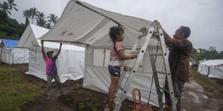 Pengungsi Gunung Agung membangun tenda untuk keluarganya di Desa Rendang, Karangasem, Bali, Sabtu (25/11/2017). Pusat Vulkanologi dan Mitigasi Bencana Geologi (PVMBG) mencatat adanya penurunan kegempaan Gunung Agung pascaletusan freatik pada Selasa (21/11) namun tetap merekomendasikan masyarakat dan wisatawan tidak berada di kawasan berjarak hingga 7,5Km dari kawah gunung yang masih berstatus siaga itu.