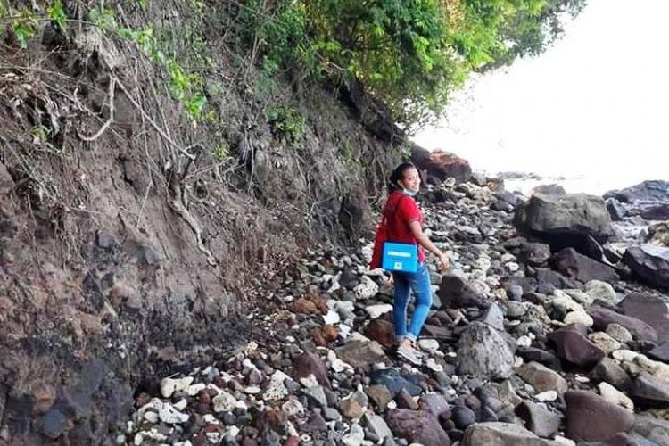 Foto : Saat Maria Mahendra Charolin (28), seorang perawat yang bertugas di Pulau Palue, Kabupaten Sikka, NTT menyusuri jalan berbatu menuju rumah rumah warga.