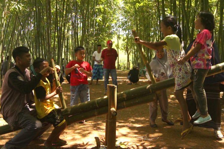 pengunjung Wisata kampung Bambu menikmati ermainan jungkat jungkit yang terbuat dari batang bambu