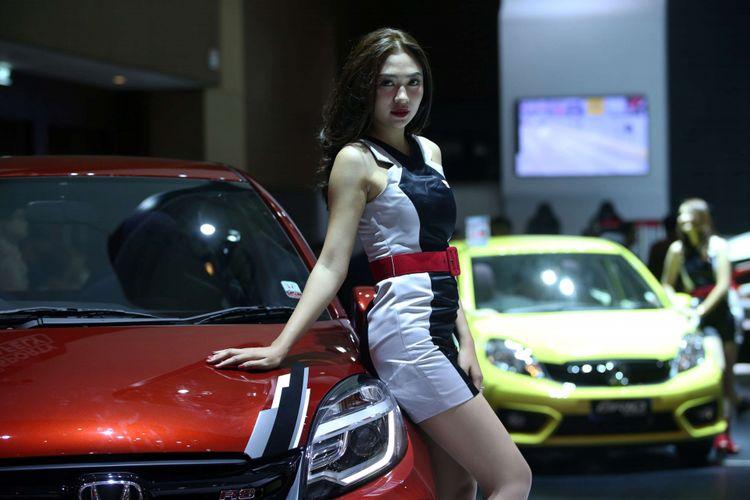 Sales Promotion Girl berpose di samping mobil yang dipamerkan di Indonesia International Motor Show 2018 di JI Expo Kemayoran, Jakarta, Jumat (20/4/2018). Pameran otomotif terbesar di Indonesia ini akan berlangsung hingga 29 April 2018 mendatang.