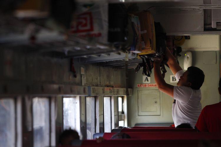 Pemudik tujuan Jawa Timur menata barang bawaanya saat berada di dalam kereta api Kertajaya di Stasiun Pasar Senen, Jakarta, Senin (13/7/2015). PT KAI mempersiapkan sekitar 370 rangkaian kereta untuk mengakomodir 96.000 pemudik tiap harinya selama arus mudik dan balik.