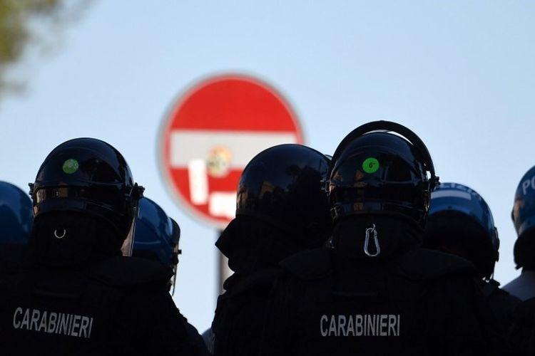 Polisi anti huru hara dan petugas kepolisian Carabinieri berjaga-jaga saat demonstrasi kelompok-kelompok neo-fasis, ekstremis dan ultras dari klub-klub sepak bola Italia atas penanganan darurat virus corona oleh pemerintah, pada 6 Juni 2020 di Circus Maximus ( Circo Massimo) di Roma, ketika negara itu melakukan lockdown yang bertujuan untuk menghentikan penyebaran infeksi Covid-19.