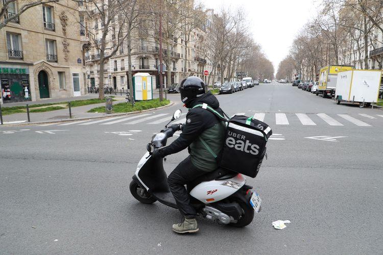 Seorang driver Uber Eats melintas di Paris, Perancis, pada 22 Maret 2020, saat lockdown ketat diterapkan untuk menekan penyebaran Covid-19.