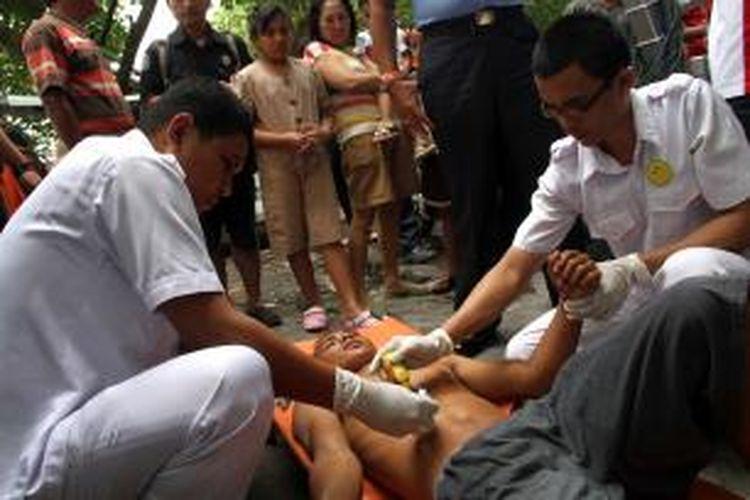 Seorang nelayan dari kapal motor Tuna King mendapat pertolongan medis, Kamis (18/7/2013).