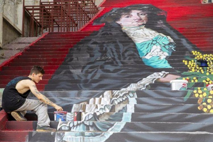 Seorang mahasiswa dari Universitas Seni Rupa Mimar Sinan melukis di atas tangga jalanan di Istanbul, Turki, pada 5 Oktober 2020.