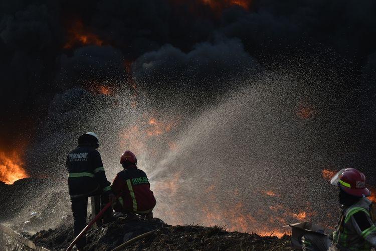 Tampak petugas pemadam kebakaran berupaya memadamkan amukan api pada pipa pertamina yang bocor akibat pengerjaan proyek di Jalur KCIC,  Selasa (22/10/2019).
