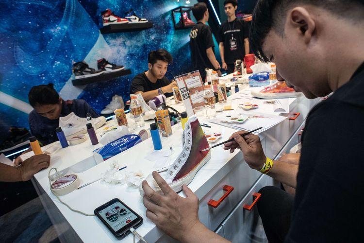 Peserta mengikuti lokakarya melukis sepatu dalam Urban Sneaker Society (USS) 2019 di District 8, kompleks SCBD, Jakarta, Jumat (8/11/2019). USS 2019 yang berlangsung hingga 10 November 2019 itu menghadirkan lebih dari 150 merek sepatu sneaker dan streetwear asal Indonesia maupun mancanegara.
