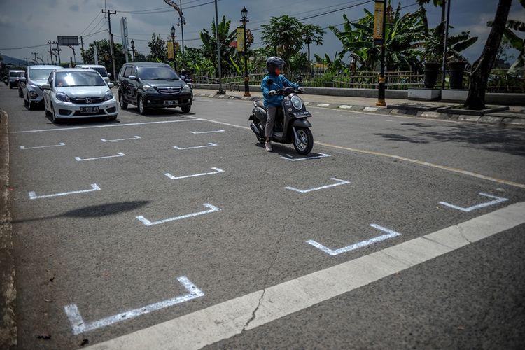 Pengendara motor berhenti di garis yang dibuat secara berjarak di  perempatan Pemda Soreang, Kabupaten Bandung, Jawa Barat, Kamis (16/7/2020). Pembuatan jarak bagi pengendara sepeda motor tersebut ditujukan untuk mengantisipasi penyebaran COVID-19 di kawasan umum.