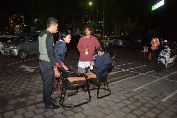 Korban gempa berada di Klinik Kimia Farma di Denpasar, Bali, Minggu (5/8/2018). Gempa berkekuatan 7 pada skala richter (SR) yang mengguncang Bali dan NTB mengakibatkan kerusakan sejumlah bangunan di kawasan Denpasar dan sekitarnya.