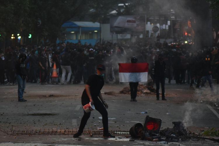 Aksi Unjuk Rasa di Bandung kembali ricuh, Senin (30/9/2019). Tampak seseorang sedang memadamkan api yang dibakar aksi massa.