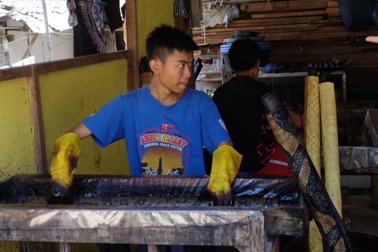 Penduduk Desa Giriloyo mewarnai kain batik di teras rumah.
