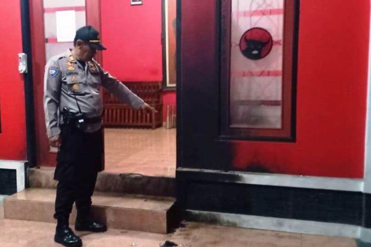 Seorang anggota Polri memerlihatkan kondisi pintu depan kantor sekretariat PDI-P Cianjur yang terbakar setelah dilempari bom molotov orang tak dikenal, Jumat (7/8/2020) dini hari.